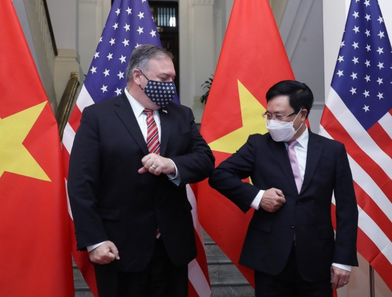This picture taken and released on 30 October 2020 by the Vietnam News Agency shows Vietnam's Foreign Minister Pham Binh Minh (R) bumping elbows to greet US Secretary of State Mike Pompeo before a meeting in Hanoi. (Bui Lam Khanh/Vietnam News Agency/AFP)