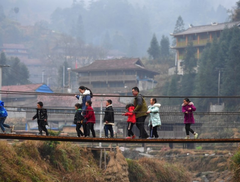 People on a bridge in a village in a Miao minority autonomous region in Liuzhou city, Guangxi, 30 January 2021. (Xinhua)