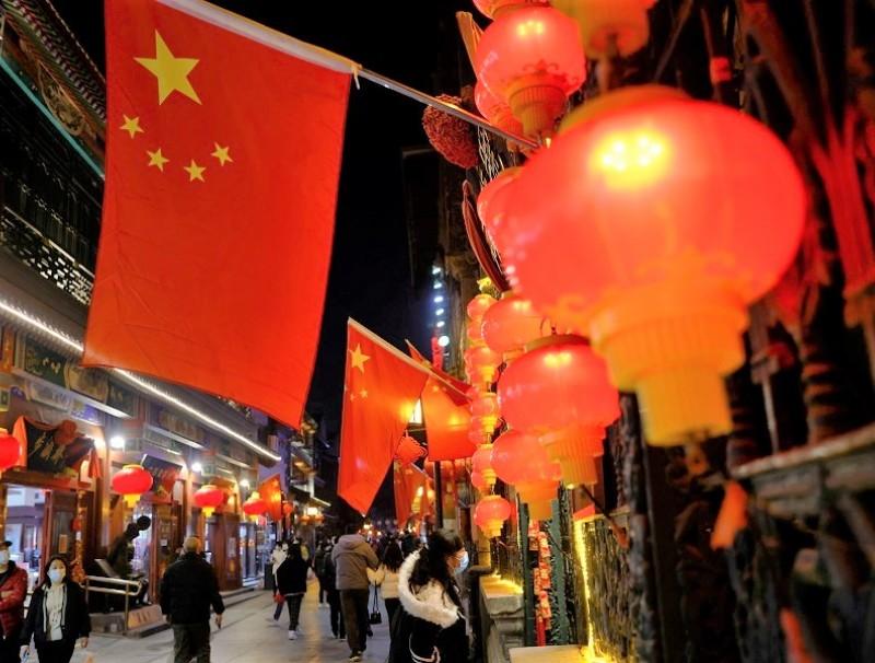 People wearing face masks walk near Qianmen Street, in Beijing, China, 10 February 2021. (Carlos Garcia Rawlins/Reuters)