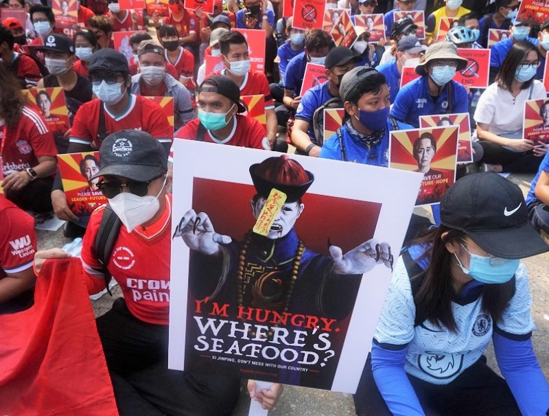 Protesters hold placards as they take part in a demonstration against the military coup, in front of the Chinese embassy in Yangon on 21 February 2021. (Sai Aung Main/AFP)