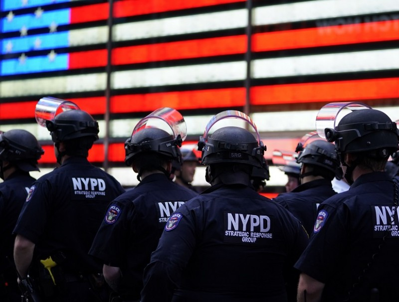 """In this file photo taken on 1 June 2020, NYPD police officers watch demonstrators in Times Square during a """"Black Lives Matter"""" protest. (Timothy A. Clary/AFP)"""