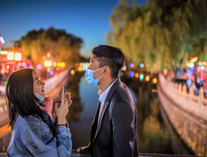 A couple wearing face masks share a laugh as they take pictures a bridge at the Hou Hai lake in Beijing on 16 October 2020. (Nicolas Asfouri/AFP)