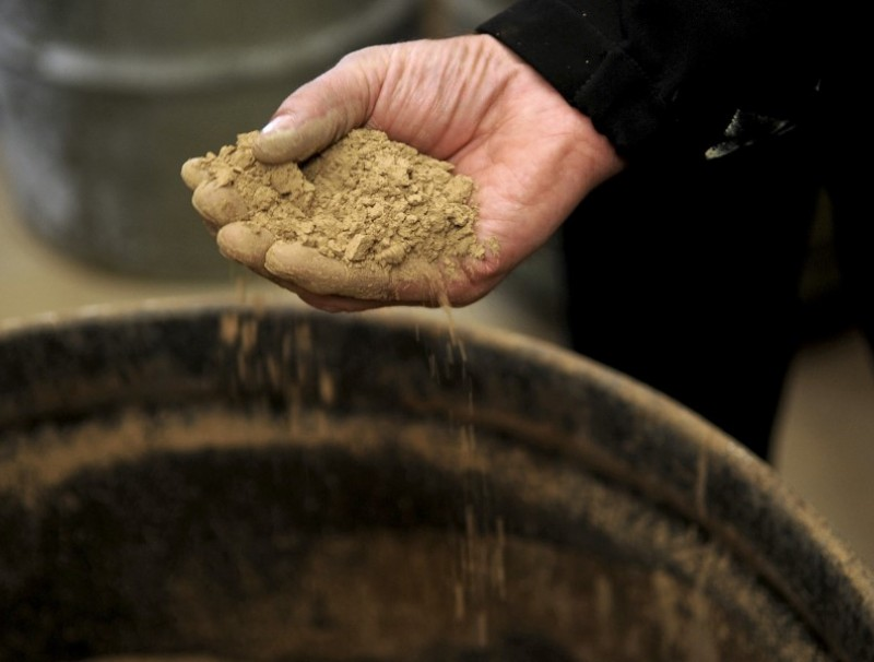 A Molycorp worker holds a handful of rocks containing rare earth elements during a media tour in Mountain Pass, California, U.S., 13 December 2010. (Jacob Kepler/Bloomberg)