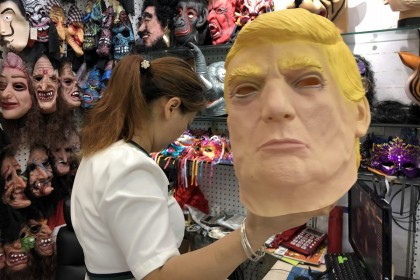 A vendor holding up a Donald Trump latex mask that she sells.