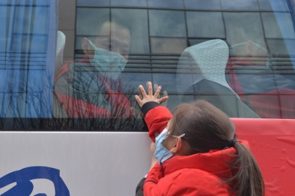 In this photo taken on 19 February 2020, a medical staff onboard a bus bids farewell to his daughter before leaving to fight the virus at the front line. (CNS)