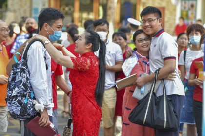 Two mothers in red qipaos hug their children at an exam centre in Hainan, 7 July 2020. (Luo Yunfei/CNS)