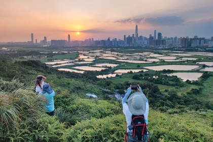 People at Ma Tso Lung village take photos of the sunset against the New Territories in northern Hong Kong, 20 October 2021. (CNS)