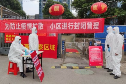 Workers in protective suits at a checkpoint for registration and body temperature measurement, at an entrance to a residential compound in Wuhan. Major leadership changes have been announced in an effort to control the epidemic. (Reuters)