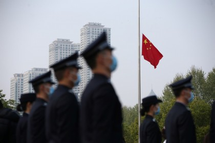 The Chinese national flag flies at half mast at a ceremony mourning those who died of the Covid-19 coronavirus as China holds a nationwide mourning on the Qingming Festival, in Wuhan, China, on 4 April 2020. (China Daily via Reuters)