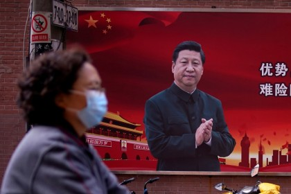 A woman walks past a portrait of Chinese President Xi Jinping on a street in Shanghai, 12 March 2020. (Aly Song/REUTERS)