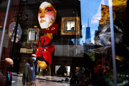 A man wearing a protective mask is reflected on a window in Chinatown during the Covid-19 outbreak in New York City, New York, US, on 17 May 2020. (Jeenah Moon/Reuters)