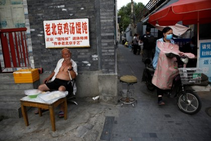 A man smokes at a stall selling frozen wonton near a hutong neighborhood in Beijing, 5 June 2020. (Tingshu Wang/REUTERS)