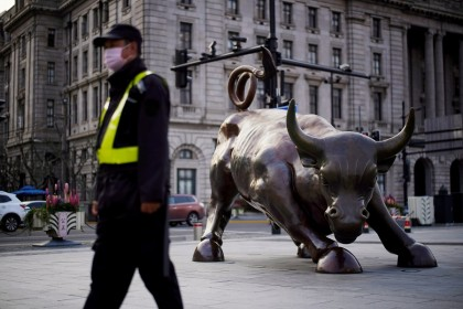 A security guard wearing a face mask walks past the Bund Financial Bull statue, on The Bund in Shanghai, China, on 18 March 2020. (Aly Song/File Photo/Reuters)
