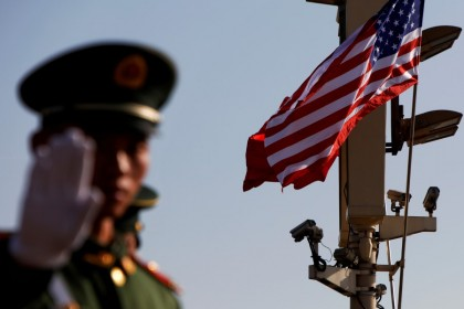 A paramilitary policeman gestures under a pole with security cameras, U.S. and China's flags, near the Forbidden City, ahead of a visit by U.S. President Donald Trump to Beijing, 8 November 2017. (Damir Sagolj/REUTERS)