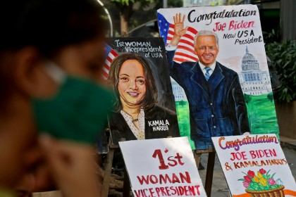A girl sits next to the paintings of US President-elect Joe Biden and Vice President-elect Kamala Harris on display alongside a road in Mumbai, India, 8 November 2020. (Niharika Kulkarni/Reuters)