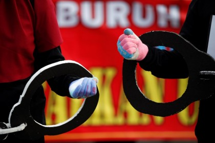 "Members of Indonesian Trade Unions carry giant handcuffs during a protest against the government's labor reforms in a ""job creation"" bill in Jakarta, Indonesia, 10 November 2020. (Willy Kurniawan/REUTERS)"