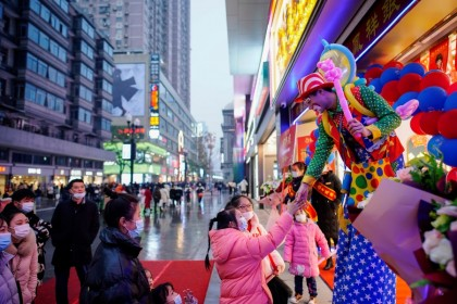 A clown interacts with people at a main shopping area in Wuhan, Hubei province, China, 6 December 2020. (Aly Song/REUTERS)