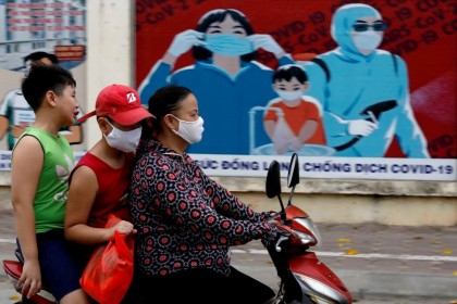 A woman wears a protective mask as she drives past a banner promoting prevention against the coronavirus disease (COVID-19) in Hanoi, Vietnam, 31 July 2020. (Kham/REUTERS)