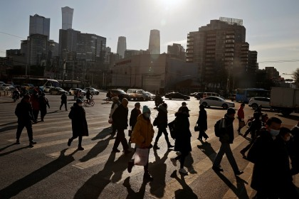People cross a street during morning rush hour in Beijing, China, 15 December 2020. (Thomas Peter/Reuters)