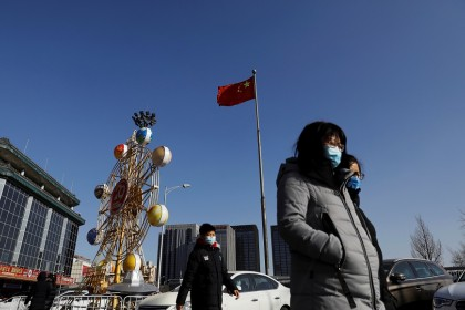 People wearing face masks walk past a Chinese flag in Beijing, China, 11 January 2021. (Tingshu Wang/Reuters)