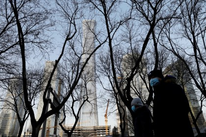 People wearing face masks walk past the China Zun skyscraper at the central business district in Beijing, China, 15 January 2021. (Tingshu Wang/Reuters)