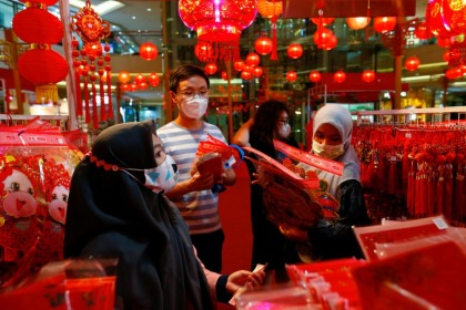 Vendors wearing protective masks serve their customers inside a stall selling decorations, ahead of the Lunar New Year, following the coronavirus disease (Covid-19) outbreak, at a shopping mall in Jakarta, Indonesia, 11 February 2021. (Ajeng Dinar Ulfiana/Reuters)
