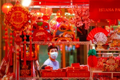 A man wearing a protective mask shops for decorations at a shopping mall ahead of the Lunar New Year, in Jakarta, Indonesia, 11 February 2021. (Ajeng Dinar Ulfiana/Reuters)