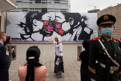 "Visitors look at a reproduction of street art by US artist Pony Wave that is part of an exhibition titled ""Art for the People"" on display at the US Embassy in Beijing, China, 21 April 2021. (Thomas Peter/Reuters)"