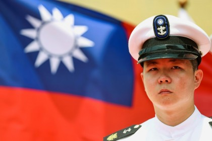 """A Taiwan Navy honour guard looks on in front of a Taiwan flag during the launch ceremony for the Taiwan Navy's domestically built amphibious transport dock """"Yushan"""" in Kaohsiung, Taiwan, 13 April 2021. (Ann Wang/Reuters)"""
