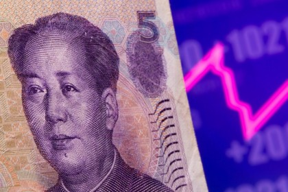 A Chinese Yuan banknote is seen in front of displayed stock graph in this illustration taken on 7 May 2021. (Dado Ruvic/Reuters)