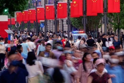 People walk along Nanjing Road, a main shopping area in Shanghai, China, 10 May 2021. (Aly Song/Reuters)
