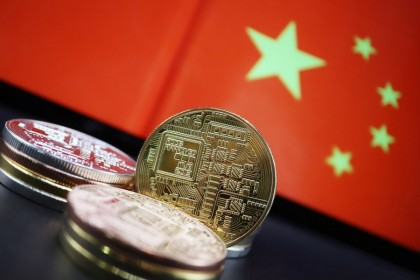Cryptocurrency representations are seen in front of an image of the Chinese flag in this illustration picture taken 2 June 2021. (Florence Lo/Reuters)