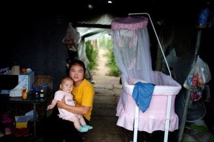 A woman and baby inside a room of a greenhouse at a village on the outskirts of Shanghai, China, 3 June 2021. (Aly Song/Reuters)