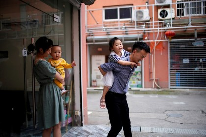 A couple plays with their two children on the outskirts of Shanghai, China, 3 June 2021. (Aly Song/Reuters)