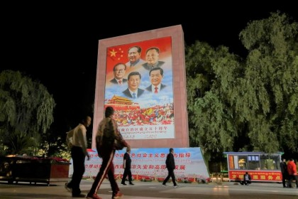 People walk past a poster showing Chinese President Xi Jinping and former Chinese leaders Mao Zedong, Deng Xiaoping, Jiang Zemin and Hu Jintao on the Potala Palace Square during a government-organised media tour to Lhasa, Tibet Autonomous Region, China, 1 June 2021. (Martin Pollard/Reuters)