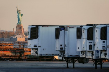 Refrigerated tractor trailers used to store bodies of deceased people are seen at a temporary morgue, with the Statue of Liberty seen in the background, during the Covid-19 outbreak, in the Brooklyn borough of New York City, US, 13 May 2020. (Brendan McDermid/Reuters)