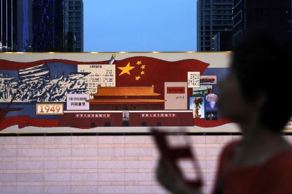 A woman walks past a decorated board with images of Tiananmen Gate and the Chinese national flag, marking the 100th founding anniversary of the Communist Party of China, at a hi-tech industrial park in Beijing, China, 23 June 2021. (Tingshu Wang/Reuters)