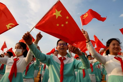 Performers wave national and party flags as they rehearse before the event marking the 100th founding anniversary of the Communist Party of China, at Tiananmen Square in Beijing, China, 1 July 2021. (Carlos Garcia Rawlins/Reuters)