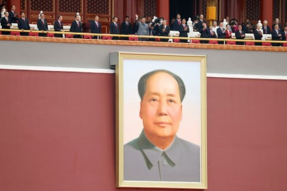 Chinese President Xi Jinping waves above a giant portrait of late Chinese chairman Mao Zedong at the end of the event marking the 100th founding anniversary of the Communist Party of China, on Tiananmen Square in Beijing, China, 1 July 2021. (Carlos Garcia Rawlins/Reuters)