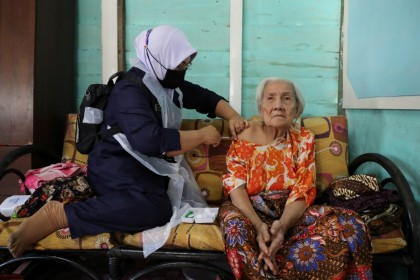A woman gets a shot of Sinovac coronavirus disease (Covid-19) vaccine at home, administered by a healthcare worker in Sabak Bernam, Malaysia, 1 July 2021. (Lim Huey Teng/Reuters)
