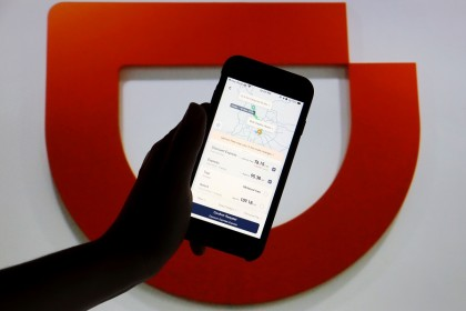 The app of Chinese ride-hailing giant Didi is seen on a mobile phone in front of the company logo displayed in this illustration picture taken on 1 July 2021. (Florence Lo/Illustration/File Photo/Reuters)
