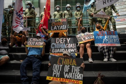 Activists stage a protest outside the Chinese Consulate, guarded by Philippine police, on the fifth anniversary of an international arbitral court ruling invalidating Beijing's historical claims over the waters of the SouthChinaSea, in Makati City,Philippines, 12 July 2021. (Eloisa Lopez/Reuters)