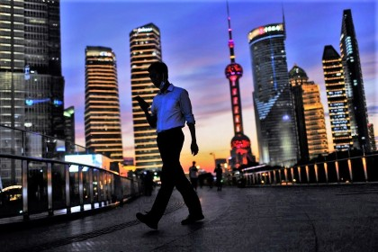A man checks his phone while walking in Lujiazui financial district during sunset in Pudong, Shanghai, China, 13 July 2021. (Aly Song/Reuters)