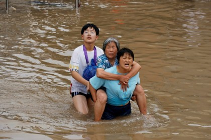 A woman carries an elderly woman as they make their way through floodwaters following heavy rainfall in Zhengzhou, Henan province, China, 23 July 2021. (Aly Song/Reuters)