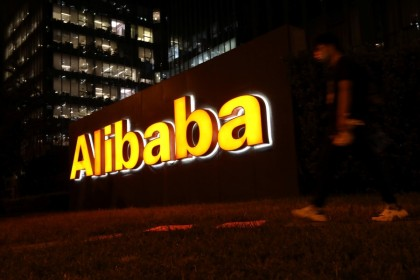 A man walks past a logo of Alibaba Group at its office building in Beijing, China, 9 August 2021. (Tingshu Wang/Reuters)