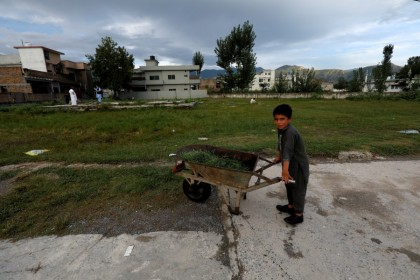 A boy stands with a wheelbarrow at the demolished former compound of Osama bin Laden in Abbottabad, Pakistan, 10 September 2021. (Akhtar Soomro/Reuters)