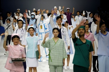 Models gesture as they present creations for medical professionals, which are designed by Beijing Institute of Fashion Technology in collaboration with Dishang, during China Fashion Week in Beijing, China, 11 September 2021. (Tingshu Wang/Reuters)