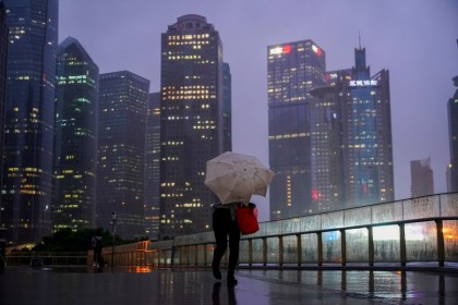 A woman walks with an umbrella amid rainfall in Shanghai, China, 13 September 2021. (Aly Song/Reuters)