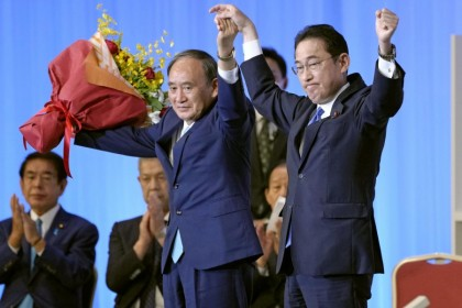 Japan's newly elected Liberal Democratic Party (LDP) leader Fumio Kishida and his predecessor Yoshihide Suga stand on stage following the LDP leadership vote in Tokyo, Japan, 29 September 2021. (Kyodo/via Reuters)