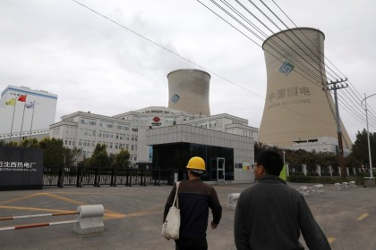People walk past a China Energy coal-fired power plant in Shenyang, Liaoning province, China, 29 September 2021. (Tingshu Wang/Reuters)